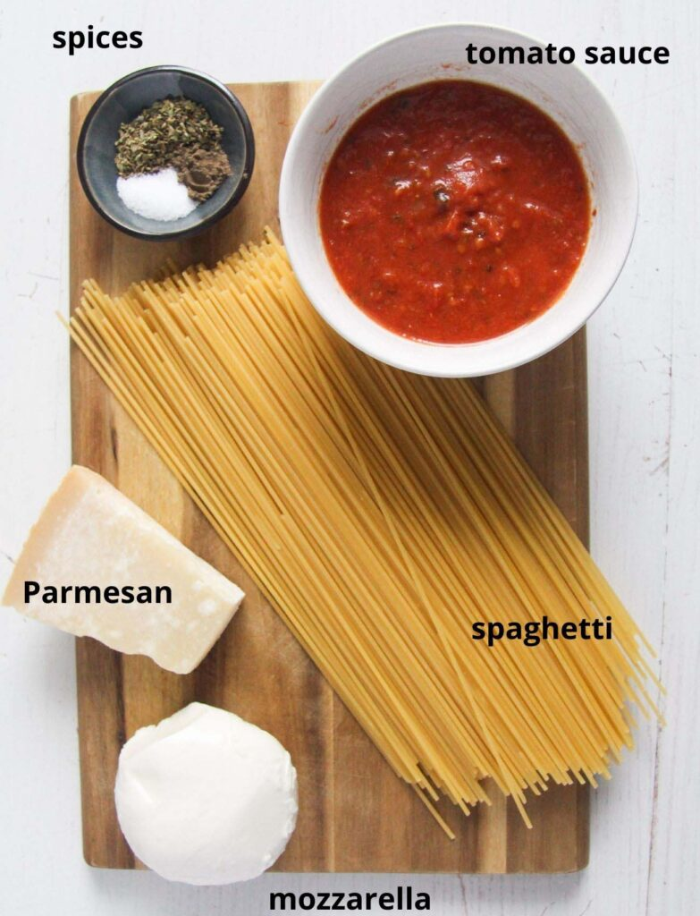 the ingredients for Fried Spaghetti - pasta, mozzarella, parmesan, tomato sauce, spices on a wooden board.