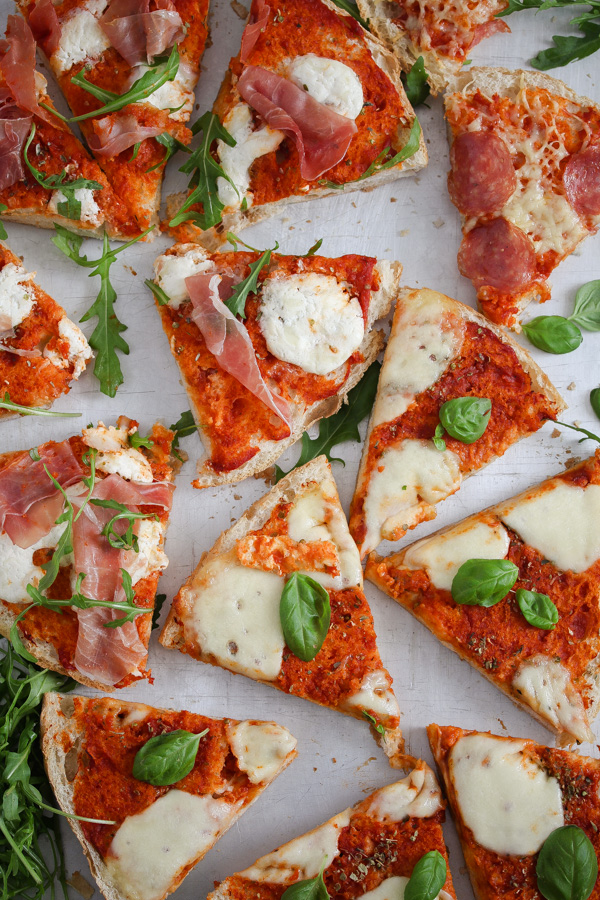 overhead view of margherita flatbread topped with tomatoes and cheese.