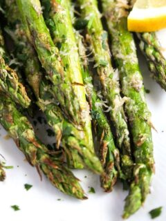 close up of air fryer asparagus sprinkled with parmesan on a white plate.