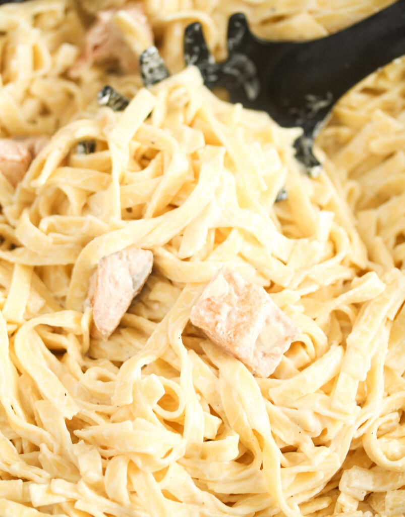 close up of creamy tagliatelle being lifted from the pan.