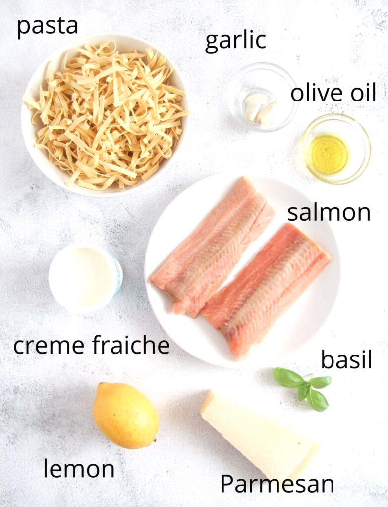 ingredients for Salmon Crème Fraiche Pasta recipe - salmon, pasta, oil, basil, creme fraiche, lemon on a table.