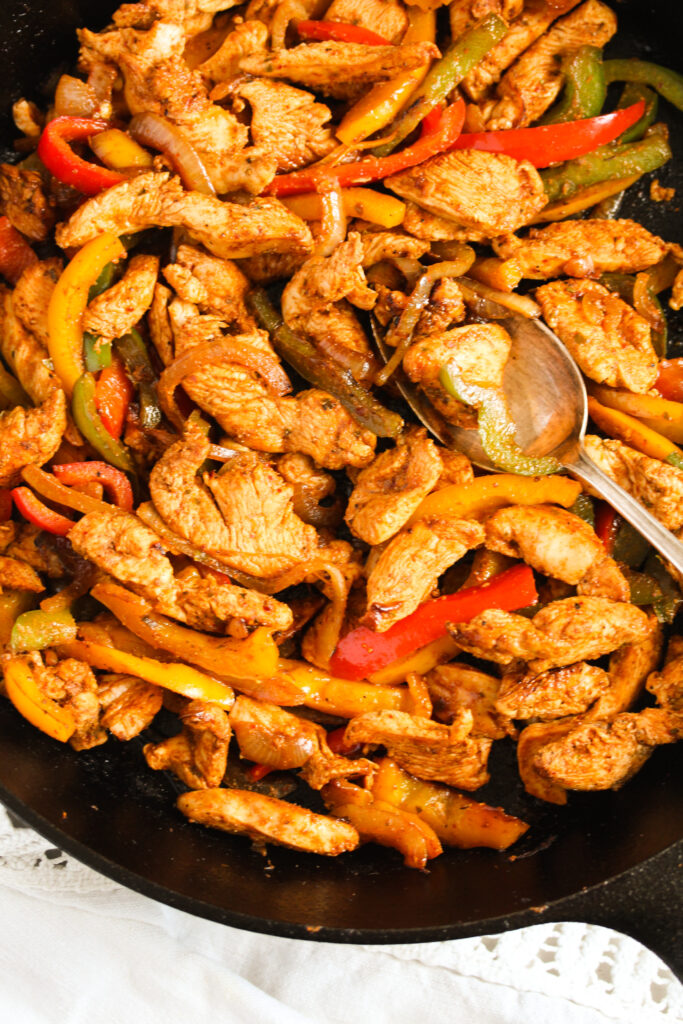 meat, peppers and onion slices cooked in a heavy bottomed pan with a spoon in it.