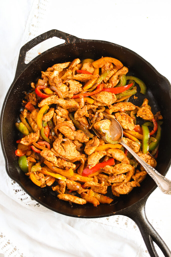 mexican chicken fajita tacos with peppers and onions in a cast iron pan.