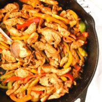 easy chicken fajita tacos close up in a cast iron skillet.