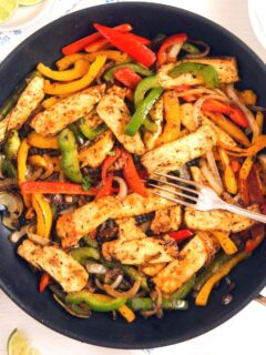 halloumi fajitas in a pan with a fork on top.