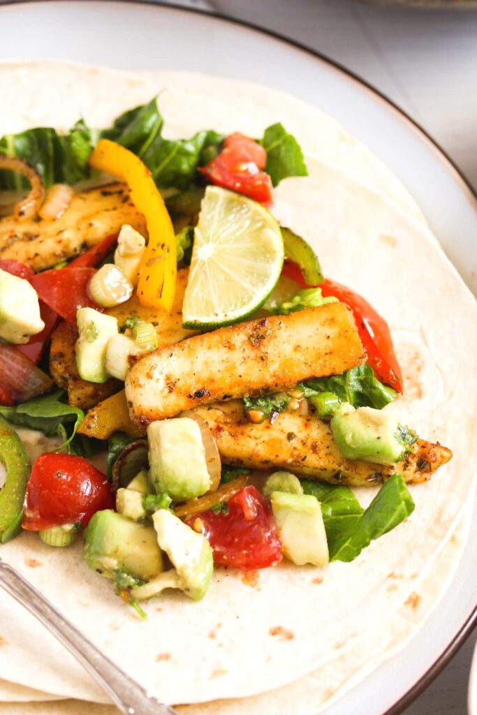 close up of a tortilla on a plate covered with fried cheese slices, peppers, onions, avocado and lime wedges.