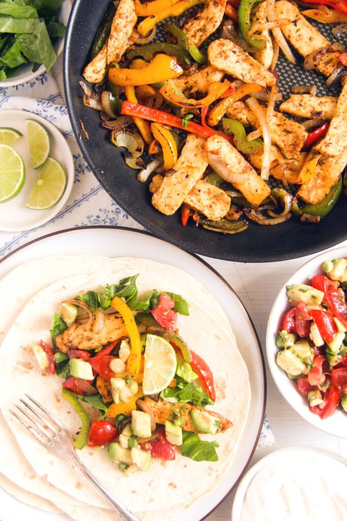 tortillas with halloumi on top and fajitas with peppers in the pan behind.