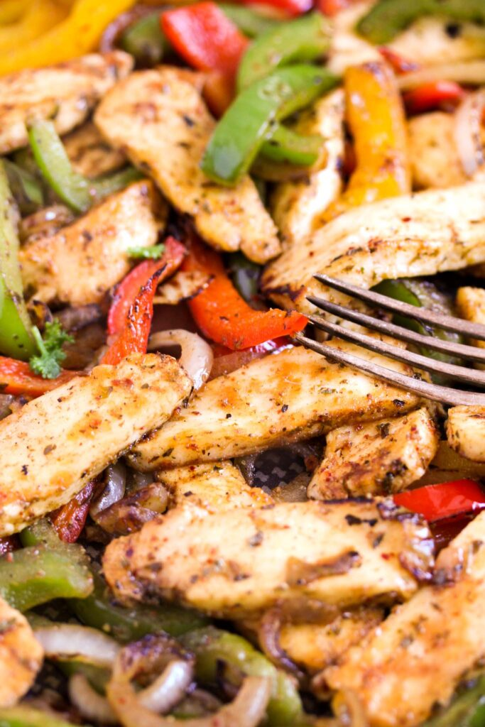 close up of strips of fried cheese, colorful peppers and onions with a fork.