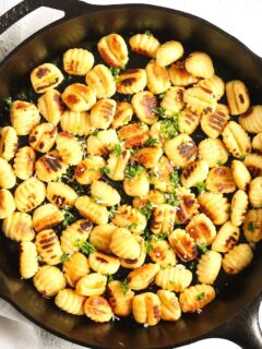 fried gnocchi in a cast-iron pan sprinkled with parsley.