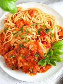 chicken pomodoro garnished with fresh basil on a small white plate.