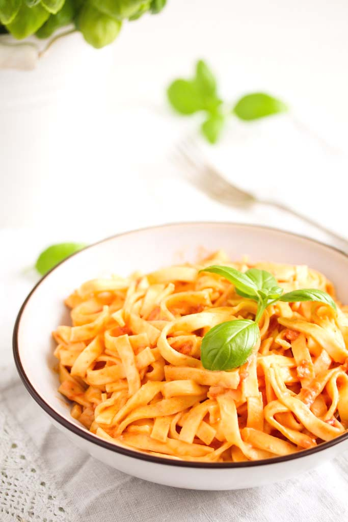 a bowl of tagliatelle with sauce and a basil plant in a white flower pot.