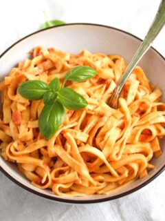 mascarpone pasta with basil leaves in a small bowl with a fork sticking inside.