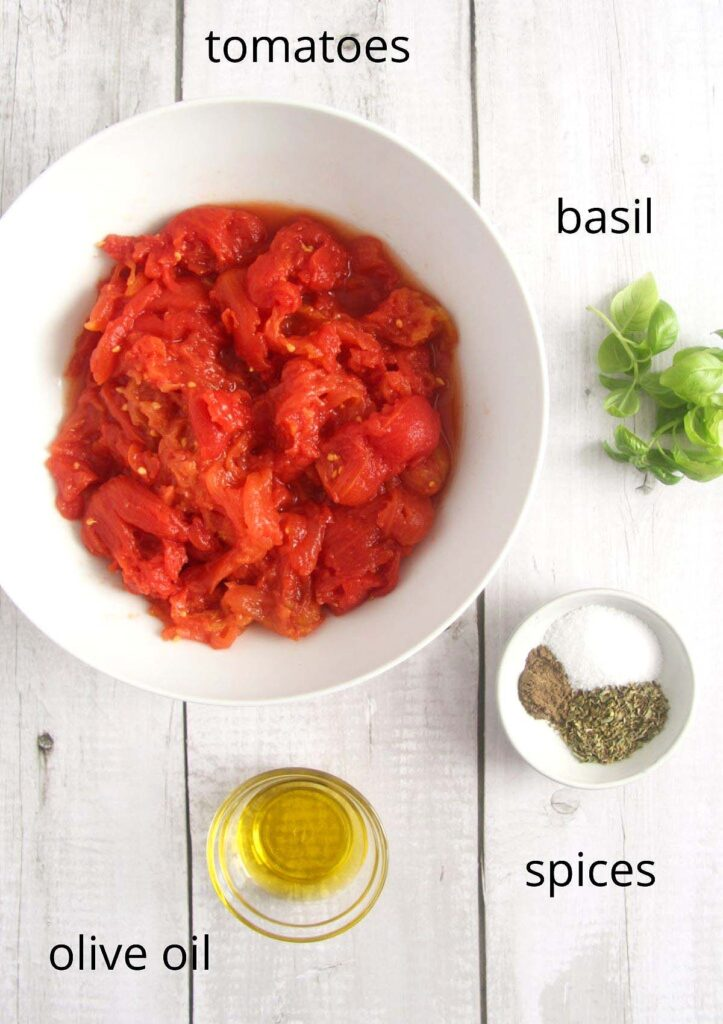 bowl with canned tomatoes, basil, olive oil and spices on a wooden table.