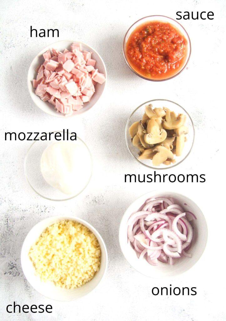 bowls with ham, tomato sauce, mozzarella, mushrooms, cheese, onions.