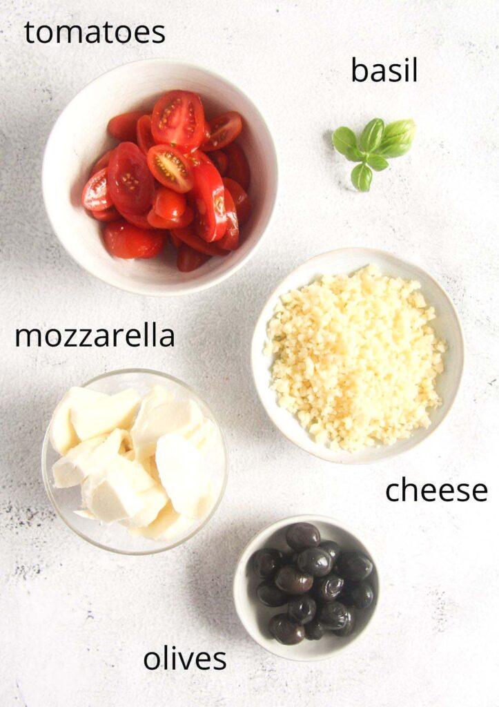 bowls with tomatoes, basil, mozzarella, cheese, olives.