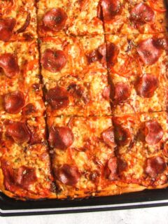 overhead view of sliced sheet pan pizza topped with cheese and salami.