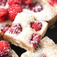 stapled cake dusted with icing sugar with berries around it.