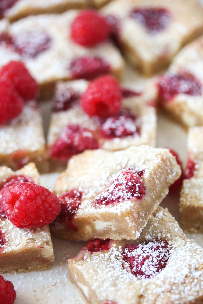 many blondies dusted with icing sugar and topped with berries.