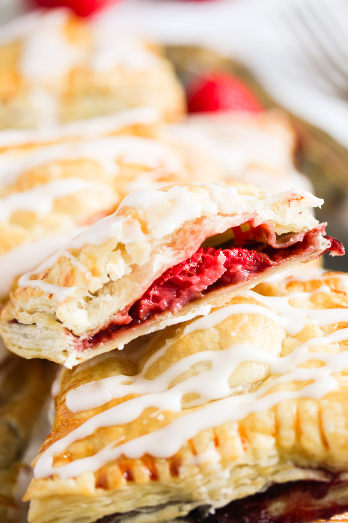two turnovers, one cut showing the berry filling.