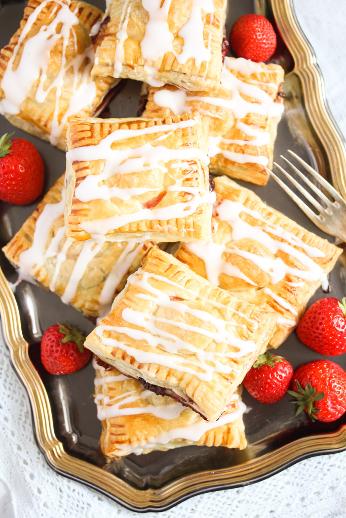 overhead view of puff pastry squares and fresh strawberries on a vintage platter with a fork.