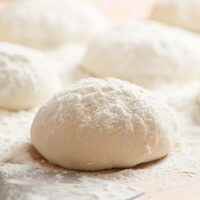 balls of thermomix pizza dough sprinkled with flour on a table.