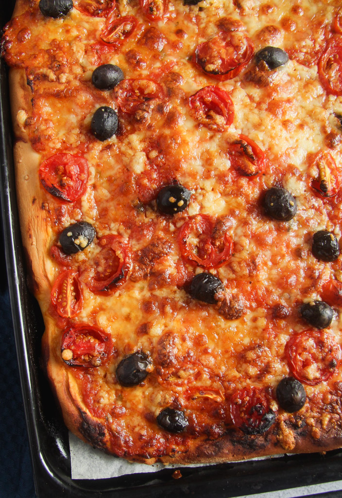 pizza with olives on the baking tray.