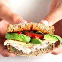 boy showing the inside of a avocado and turkey sandwich with tomatoes and mayo.