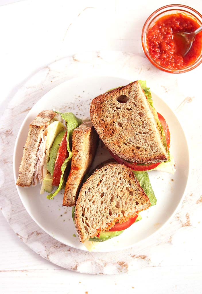 overhead view of halved turkey avocado sandwiches on a white plate served with chili sauce.
