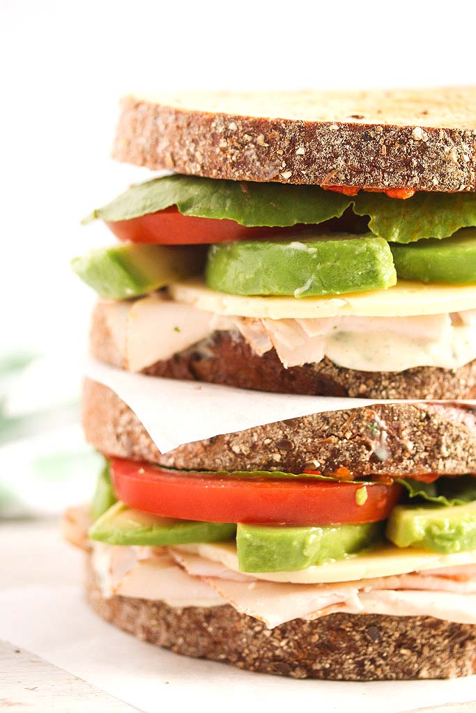 two stapled sandwiches with avocado, turkey, tomato and lettuce.