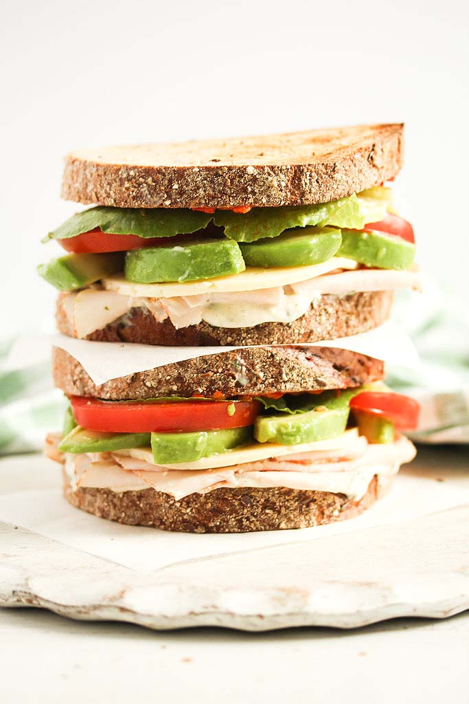 tall sandwich filled with avocado and turkey.