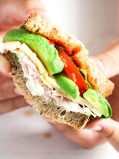 boy's hands holding a halved turkey avocado sandwich.