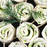 many small pinwheels with cucumber and cream cheese decorated with fresh dill.