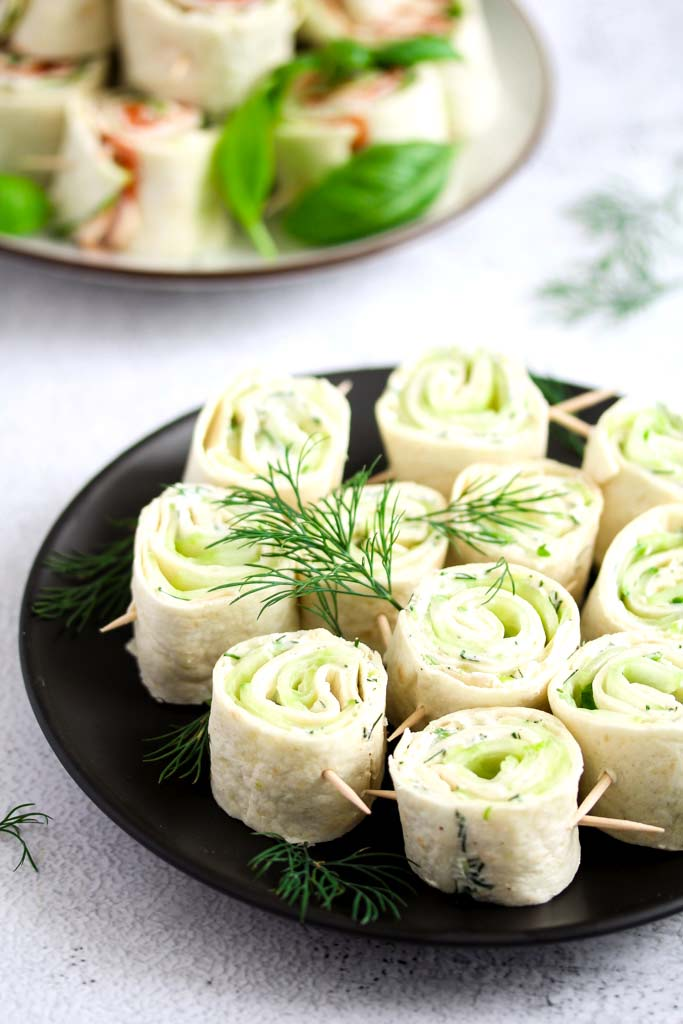 cucumber tortilla wraps sliced and arranged on a black plate.