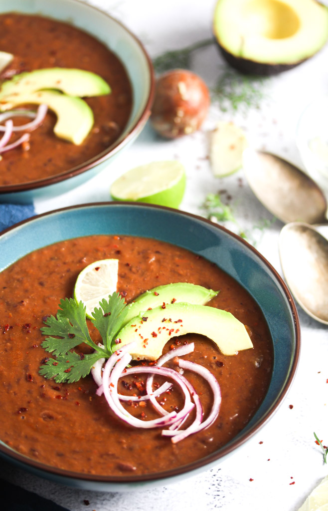two bowl of dark soup topped with avocado and onions.