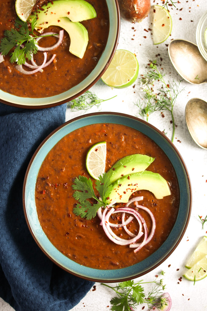 two bowls of bean dish topped with avocado and limes. Two spoons, more avocado and cilantro beside it.