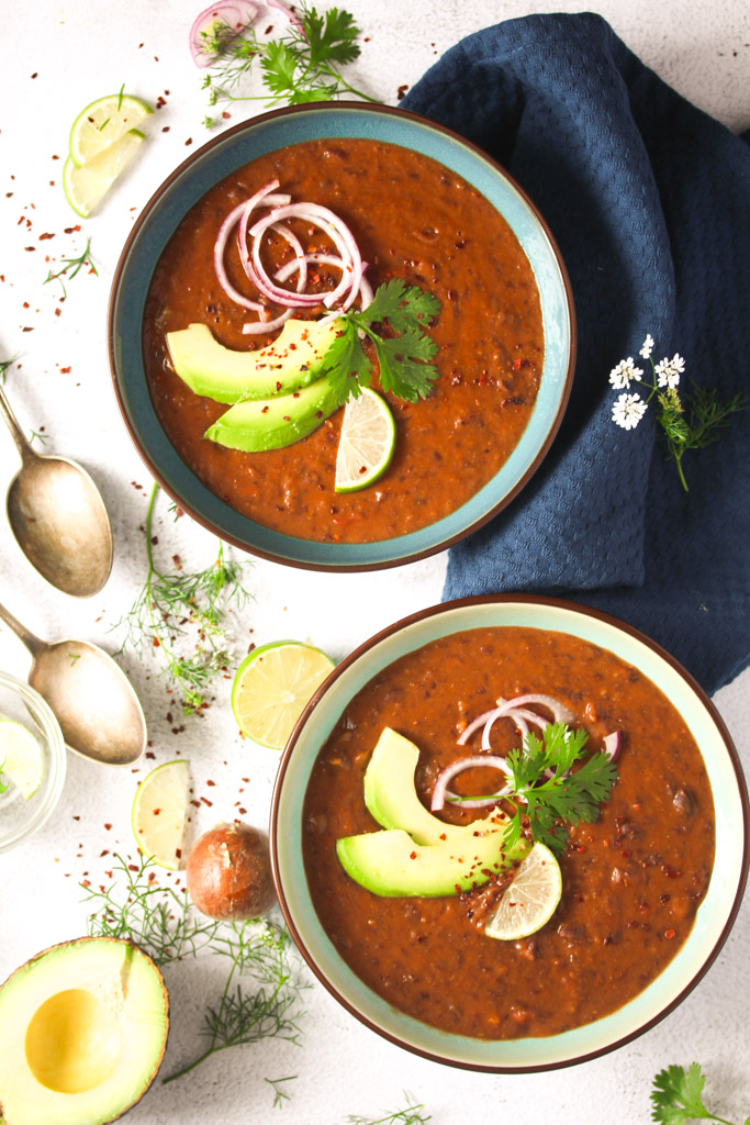 two bowls of panera copycat soup with black beans and avocado.