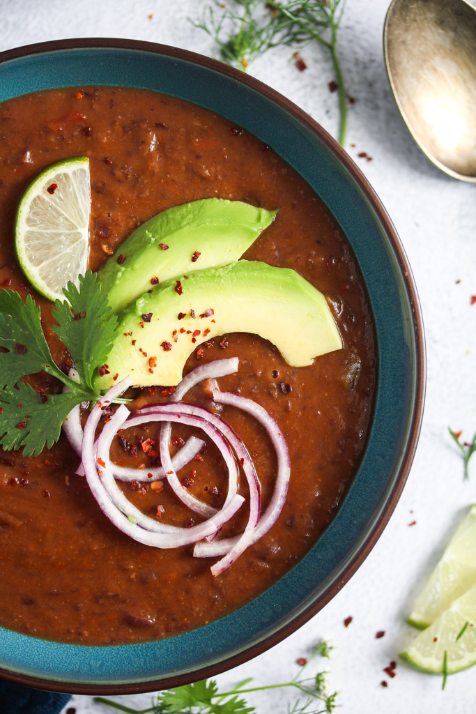 close up brown meal with avocado, lime and onions on top.