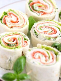 sandwich pinwheels arranged on a plate with basil leaves between them.