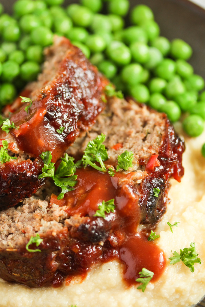 close up image of sliced meat loaf drizzled with glazed and served with peas.