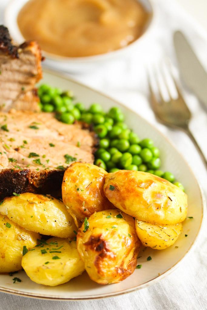 sliced pork roast with potatoes and peas close up image.