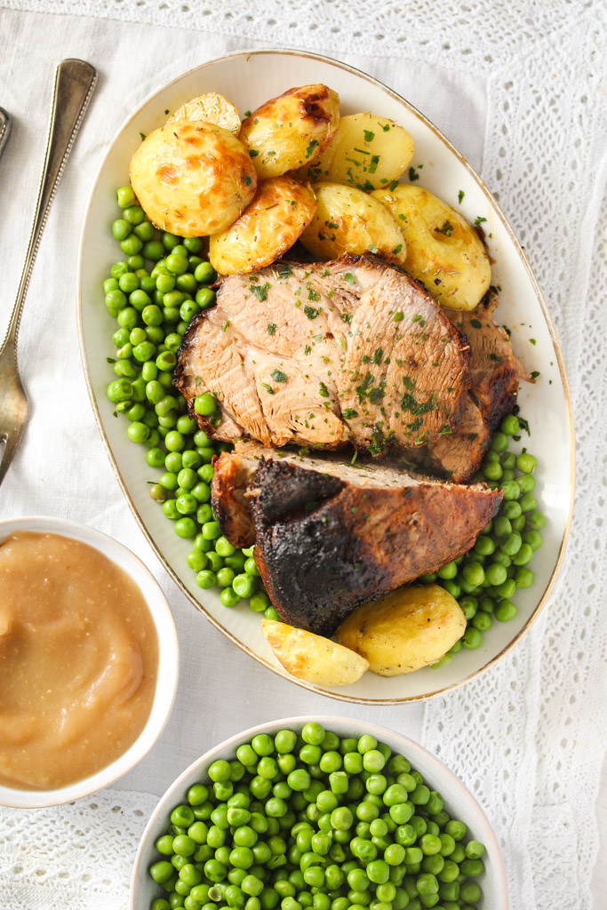 large platter with roasted meat, peas and potatoes, apple sauce bowl beside it.