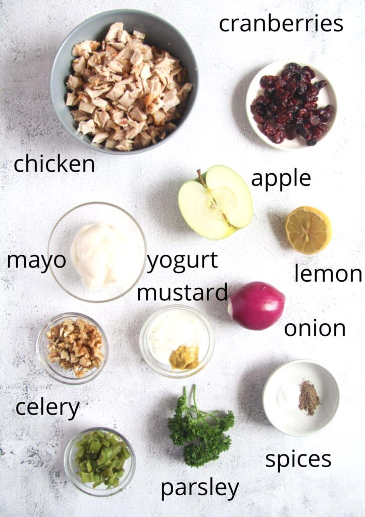 all the ingredients for chicken salad with walnuts, apples and cranberries in small bowls on the table.