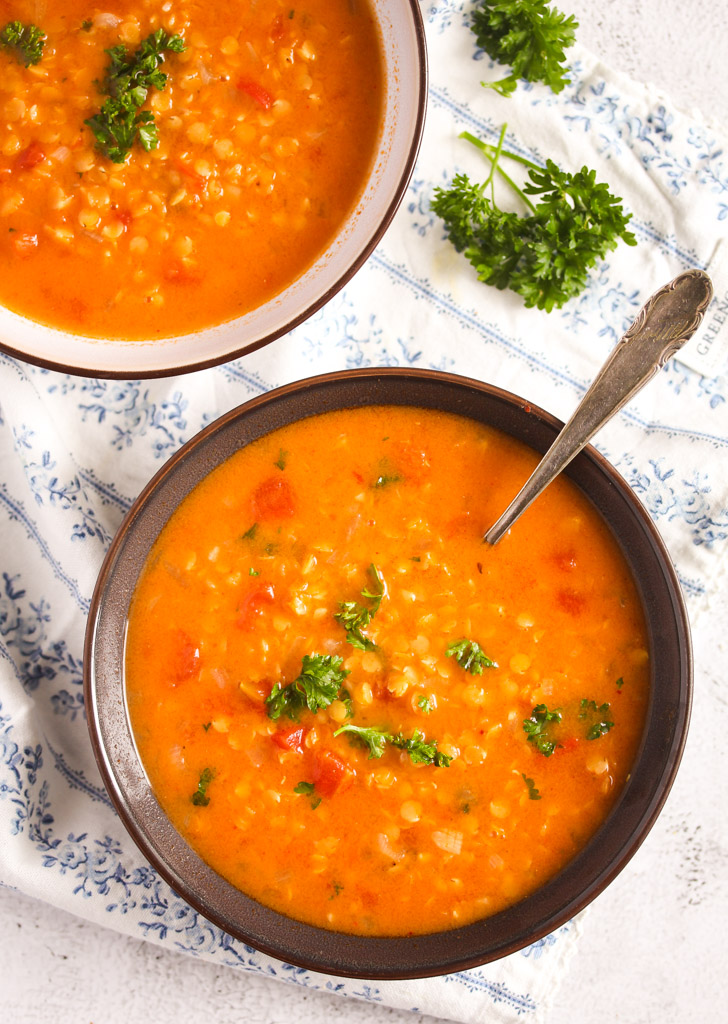 two bowls of orange colored food with lentils and tomatoes.