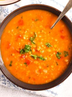 lebanese lentil soup with tomatoes and parsley in a brown bowl.