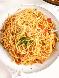 white bowl full of leftover spaghetti cooked with bacon and tomatoes.