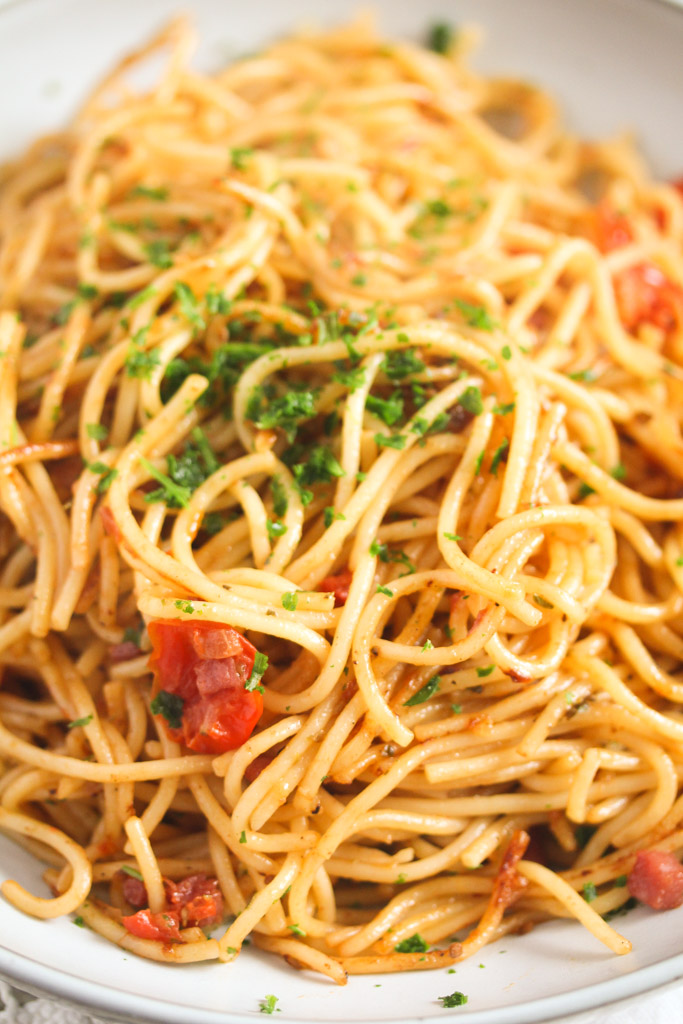 a bunch of fried leftover spaghetti sprinkled with parsley close up.