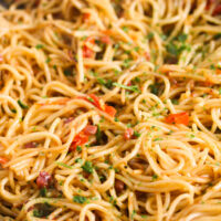 tangled noodles with bacon and tomatoes close up.