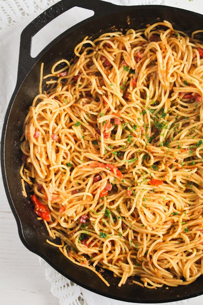 overhead view of spaghetti sprinkled with parsley in a large cast-iron skillet.
