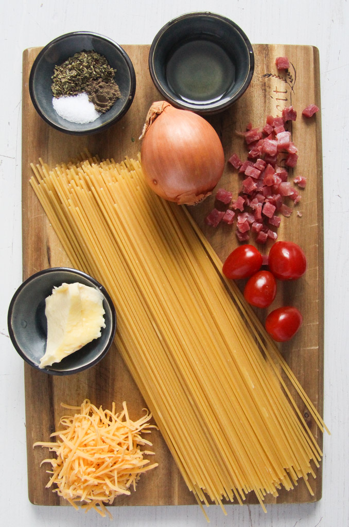 spices, oil, butter, onion, tomatoes, cheese, pasta on a cutting board.