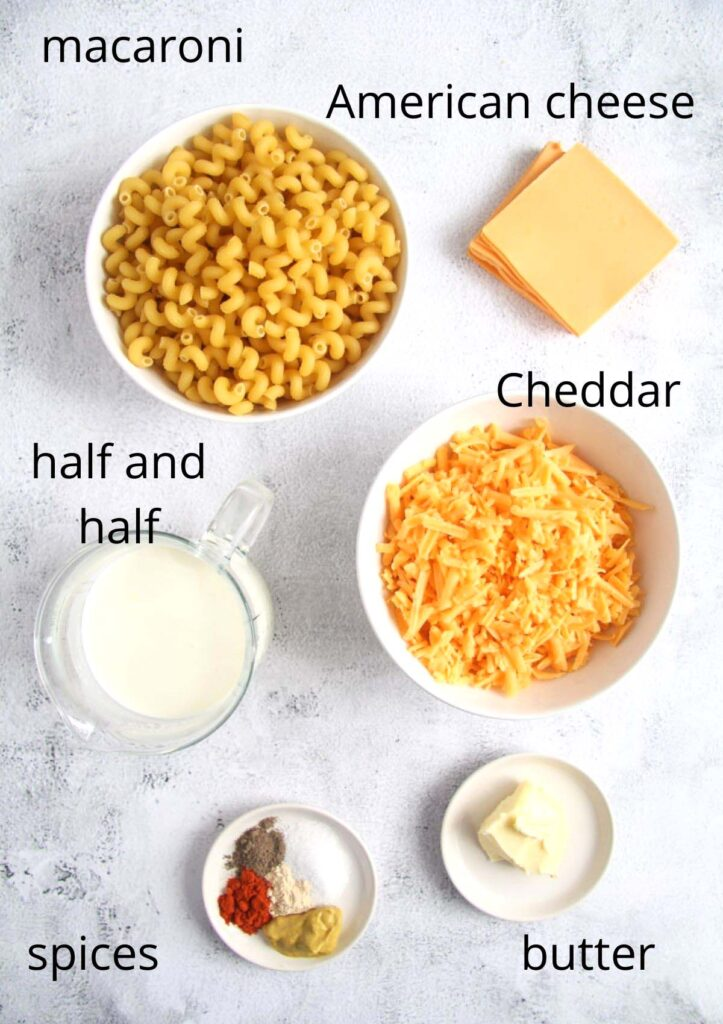 bowls with cheese, macaroni, half and half, spices and butter for making mac and cheese.